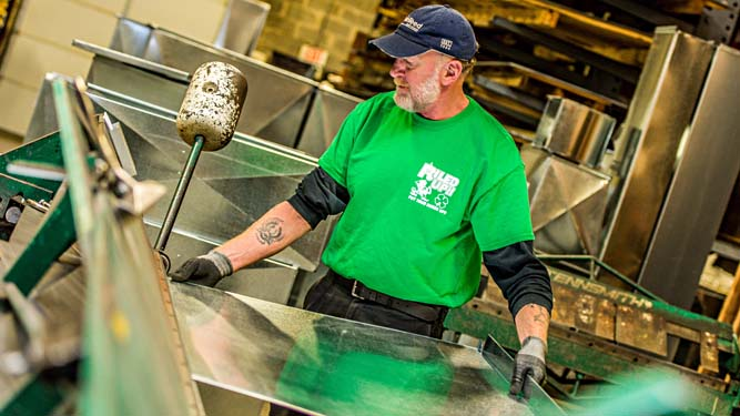 Dave working sheet metal on a machine in the Riley Industries sheet metal shop